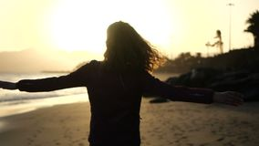 Fim do movimento lento acima da silhueta da dança da jovem mulher em uma praia com o cabelo que funde no vento que olha o por do  vídeos de arquivo