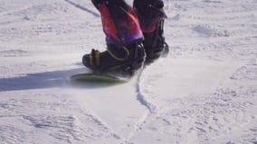 FIM DO MOVIMENTO LENTO ACIMA: Equitação do Snowboarder e salto na inclinação do esqui em montanhas nevado filme