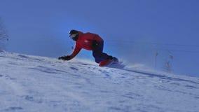 FIM DO MOVIMENTO LENTO ACIMA: Snowboarder que cinzela na neve perfeitamente preparada na estância de esqui da montanha filme