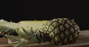 Fim do movimento lento da zorra acima do abacaxi exótico suculento fresco video do fruto em uma placa de corte em uma tabela de m filme