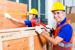 Fim do trabalhador uma caixa de madeira com martelo e prego Imagens de Stock Royalty Free