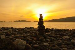 Fim equilibrado da pilha das pedras acima no mar Foto de Stock