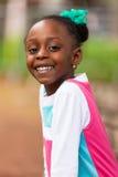 Fim exterior acima do retrato de uma menina preta nova bonito - p africano Imagem de Stock