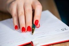 Fim fêmea bonito da mão acima com tratamento de mãos vermelho dos pregos para escrever com profundidade da pena de campo limit fotografia de stock royalty free