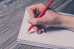 Fim lateral do perfil acima da foto da mão do ` s da pessoa que faz anotações ao caderno usando o lápis vermelho da pena Escrita  imagem de stock royalty free