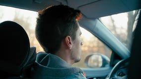 Fim médio da vista traseira acima do tiro do homem caucasiano ocasional novo que conduz seu carro filme