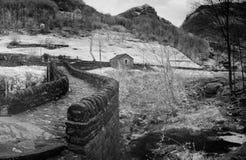 Fim preto e branco acima da vista da ponte de pedra histórica das épocas romanas em um vale isolado da montanha fotografia de stock royalty free