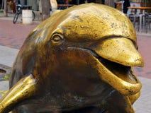 Fim principal do golfinho acima, um fragmento de uma estátua de bronze amarela do ar livre na rua imagem de stock