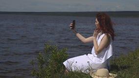 Fim sensual acima do retrato da menina bonita no vestido branco do verão no rio a menina faz um selfie fora na vídeos de arquivo