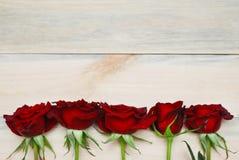 Fim vermelho de Rosess acima sobre o fundo Textured de madeira fotos de stock royalty free