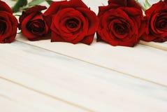 Fim vermelho de Rosess acima sobre o fundo Textured de madeira fotografia de stock