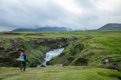 Fimmvorduhals trek in Iceland. Trekker crossing green landscape during Fimmvorduhals trek from Skogar to Porsmork passing Eyjafjallajokull eruption area Royalty Free Stock Image