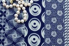 Fin aérienne de collier de perle sur le tissu d'indigo Photographie stock