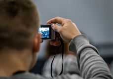 Fin arrière de vue d'un homme prenant la photo avec un appareil-photo compact Photographie stock libre de droits