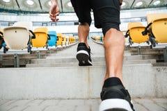Fin arrière de vue de jambes masculines dans le fonctionnement d'espadrilles Photographie stock libre de droits