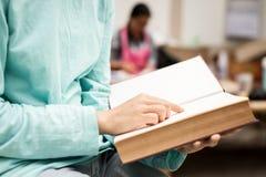 Fin asiatique de jeune fille vers le haut d'indication par les doigts à lire un livre à o images libres de droits