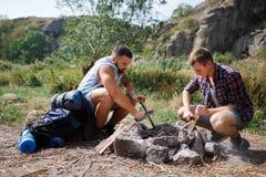 Fin d'angle faible de deux jeunes touristes masculins dans le bois, organisant le feu de camp pour le barbecue Aide Photographie stock libre de droits