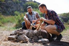 Fin d'angle faible de deux jeunes touristes masculins dans le bois, organisant le feu de camp pour le barbecue Aide Photo stock