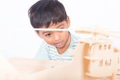 Fin d'avion en bois d'ittle de jeu asiatique mignon de garçon Photo stock