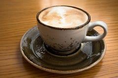 Fin d'une grande tasse de cappuccino avec la conception de mousse d'art sur une table en bois jaune dans un café confortable Image stock
