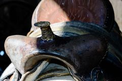 Fin d'une selle usée de cheval stockée dans une grange Images stock