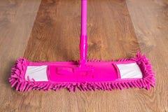 Fin de balai rose de nettoyage sur le plancher en bois - avant ensuite image stock