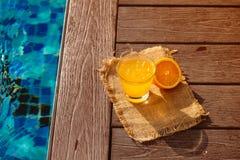 Fin de boisson d'alcool de cocktail de tournevis avec le jus, les tranches et la glace d'orange se tenant près de la piscine Limo photographie stock