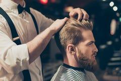 Fin de côté de profil vers le haut de portrait de vue de l'homme macho viril bel faisant couper ses cheveux dans le raseur-coiffe images stock