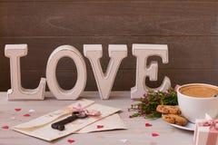 Fin de décoration de jour du ` s de Valentine  La tasse de café, les cadeaux, les fleurs et le mot aiment sur le fond en bois Clé Image stock