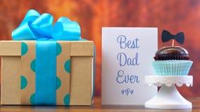 Fin de jour du ` s de père de cadeau, de petit gâteau et de carte sur le fond en bois Images stock