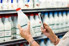 Fin de la femme supérieure prenant la photo de la bouteille à lait Photo libre de droits