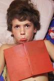 Fin de la préadolescence de garçon vers le haut de photo avec le livre dans le lit Image libre de droits