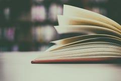 Fin de livre ouvert sur le bureau avec le fond de tache floue de filtre de vintage Photographie stock libre de droits