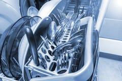 Fin de machine de lave-vaisselle, plats, renards de cuillères de couverts et couteaux dans un plateau en plastique image libre de droits
