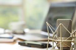 Fin de microphone de condensateur devant les WI brouillés d'un espace de travail Photographie stock libre de droits