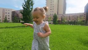 Fin de mouvement lent : bébé mignon marchant en parc de ville et aroun l'explorant du monde elle, jour ensoleillé d'été banque de vidéos