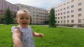 Fin de mouvement lent : bébé mignon marchant en parc de ville et aroun l'explorant du monde elle, jour ensoleillé d'été clips vidéos