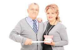 Fin de position de couples âgée par milieu tenant ensemble des dentiers et Image libre de droits