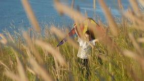 Fin de semana del ` s de los niños que juega con la cometa colorida en la playa almacen de video