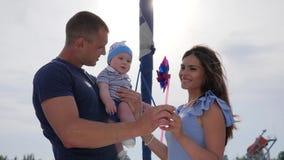Fin de semana del varón con el cónyuge y el niño al aire libre, niño en manos del papá cerca a la madre en el aire abierto, almacen de video