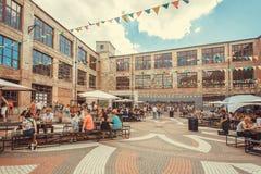 Fin de semana de la ciudad con la muchedumbre de gente que se sienta en patio del festival popular de la comida de la calle Fotos de archivo