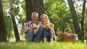 Fin de semana de la familia, par jubilado que se sienta en parque y que come las manzanas verdes, comida campestre metrajes