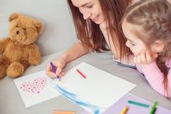 Fin de semana de la madre y de la hija junto en casa en la ayuda de la mamá del sofá para dibujar la tarjeta de felicitación imagen de archivo libre de regalías