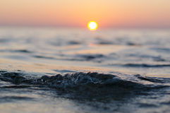 Fin de vague de mer au temps de coucher du soleil avec la réflexion rouge et orange du soleil sur l'eau Fond brouillé par abstrai Photos stock