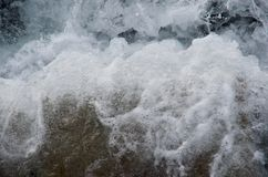 Fin de vague se brisante comme elle écume du brise-lames Image libre de droits