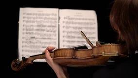 Fin de violon des arcs continuer la ficelle derrière les feuilles avec des notes Fin vers le haut Vue arrière Fond noir clips vidéos