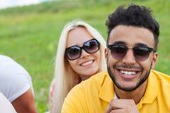 Fin de visage de couples vers le haut d'herbe verte, d'homme de course de mélange et de lunettes de soleil extérieurs de femme Photographie stock libre de droits