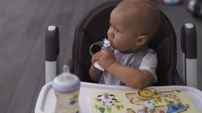 Fin de visage vers le haut de moustache blanche drôle : Jeune mère alimentant son fils de bébé garçon s'asseyant dans un siège d' banque de vidéos