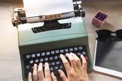 Fin de vue supérieure des mains de dame utilisant la machine à écrire p de vert de vintage images stock