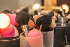 Fin des brosses de maquillage à côté d'un miroir avec des projecteurs images libres de droits